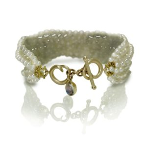 Six Strand White Pearl Bead Bracelet with two rose gold celtic spirals and oval Rainbow Moonstone cabouchon charm